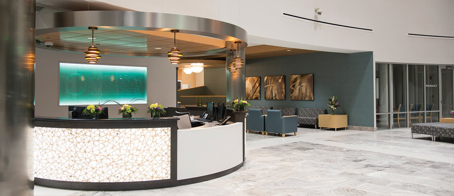 Sophisticated hospital lobby with a view through to a transitional waiting area featuring Kwalu's carrara lounge chairs and occasional tables. Perfectly designed for healthcare settings,these products are at home in any hospital lounge area.