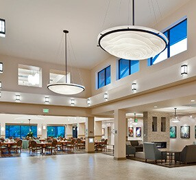 Impressive assisted living double volume lobby with sophisticated pendant lamps, elegant lounge furniture and a view of the dining room in the background, featuring Kwalu's San Michelle dining chairs.