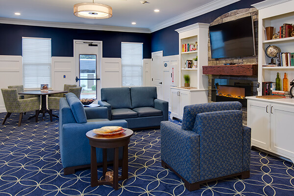 Kwalu's modern, curved arm presidio lounge chairs beautifully complement the Cortona end tables and plush Dovera lounge chairs and loveseats in this stylish senior living common area.