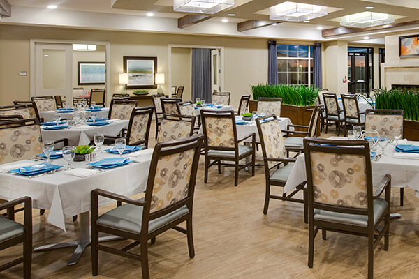 Sophisticated senior living dining room featuring Kwalu's elegant Bellariva dining chair with optional handgrip on the back for positioning residents at our dining tables.