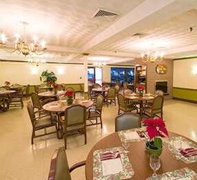 A different angle of the nursing home dining room, featuring Kwalu's regal dining chairs and pedestal dining tables.