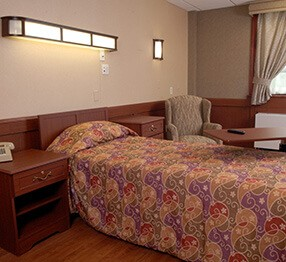 Kwalu wall protection as wainscot paneling, lancaster bedside cabinets and overbed table and fireside chair contribute to the homelike atmosphere of this nursing home resident room.