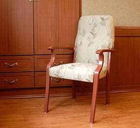 Kwalu Lancaster built-in wardrobes and virginia resident room chair are the perfect fit for this nursing home resident room.